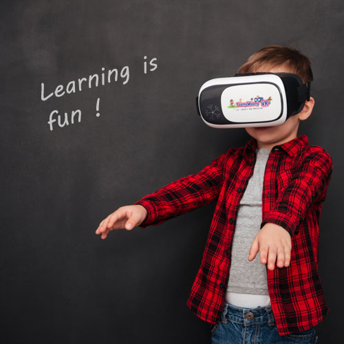 Boy with headset infront of black board with 'learning is fun' behind