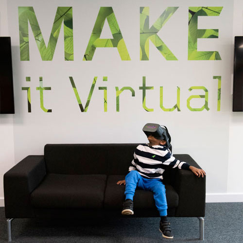 Boy with headset looking at make it virtual sign